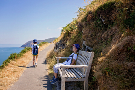 Preschool children, waling on a coastline path in Deconshire, enjoying the scenery view in the summer Stock Photo