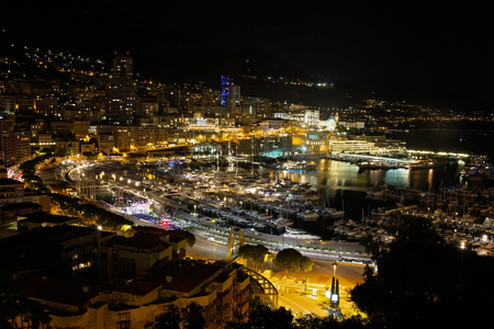 Panorama of Monte Carlo at night from the village of Monaco with Port Hercules. Buildings with illumination and yachts in harbor aerial top view