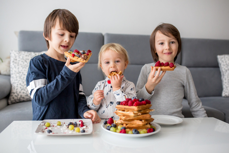 Sweet toddler birthday boy and his brothers, eating belgian waffle with raspberries, blueberries, coconut and chocolate for breakfast at home