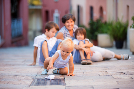 Little baby boy and his older brothers and grandmother, sitting on colorful street in the town of Villefrance, French Riviera