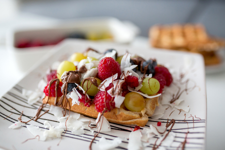 Sweet toddler birthday boy, eating belgian waffle with raspberries, blueberries, cocnut and chocolate at home Stock Photo