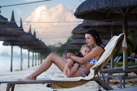 Mother, breastfeeding her toddler boy on the beach, hugging on the ocean shore, relaxing on beach chair