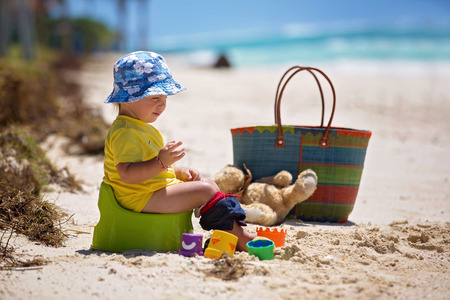 Little toddler boy, learning potty training on the beach on a tropical island Mauritius