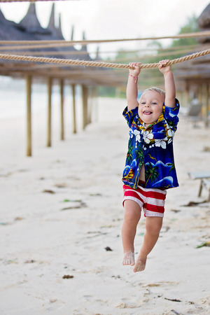 Cute toddler boy, happily hanging on rope on the beach on sunset, playful time