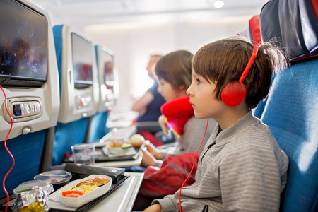Cute child, boy, watching TV on board of aircraft, traveling on vacation with parent and siblings going for a summer holiday Foto de archivo - 120399514