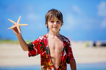 Children playing with starfish, kids happiness playful beach summer concept
