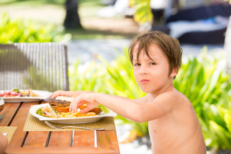 Sweet preschool boy, eating hamburger with french fries in a restaurant on beach summer resort in Mauritius