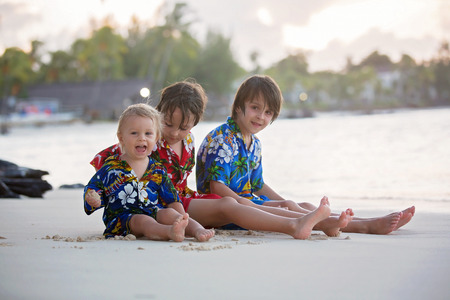 Happy beautiful fashion family, children, dressed in hawaiian shirts, playing together on the beach on sunset, famiy joyful vacation Stock Photo