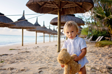 Happy beautiful fashion family, children, casually dressed, enjoying the sunrise on the beach in Mauritius, famiy joyful vacation