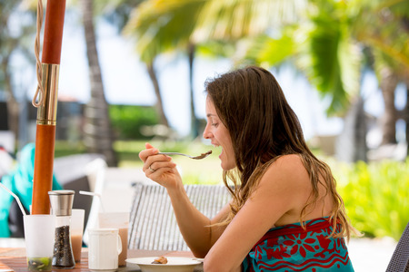 Young woman in beach wear, eating desert in a restaurant on beach summer resort in Mauritius