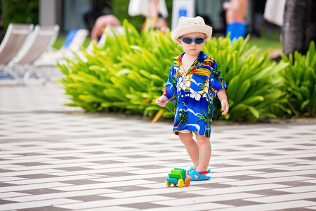 Adorable toddler boy in summer holiday resort in Mauritius, casually dressed, had and sunglasses Reklamní fotografie