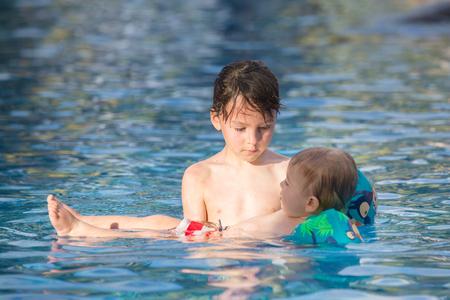 Adorable niño feliz, niño pequeño, divirtiéndose relajándose y jugando con su hermano mayor en una piscina en un día soleado durante las vacaciones de verano en el resort Foto de archivo