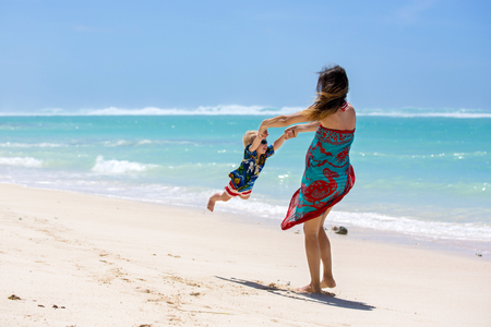 Happy beautiful fashion family, mom and children, dressed in hawaiian shirts, playing together on the beach, famiy joyful vacation