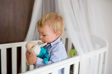 Portrait of bored baby standing in crib. Baby boy stand alone in crib. Sad little baby. Lonely baby crying in bed Stock fotó