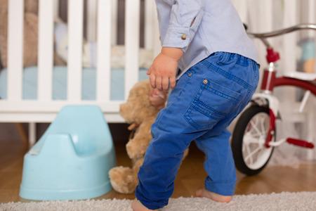 Een kleine peuterjongen, plassend in zijn broek, kon niet op tijd op het potje, spelend kind en vergetend te gaan plassen. Zindelijkheidstraining voor kinderen