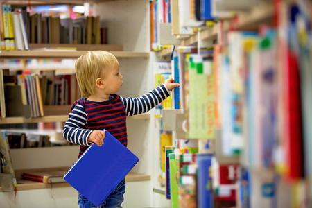 Slimme peuter, leert zichzelf op in een bibliotheek, leest boeken en kijkt naar foto's