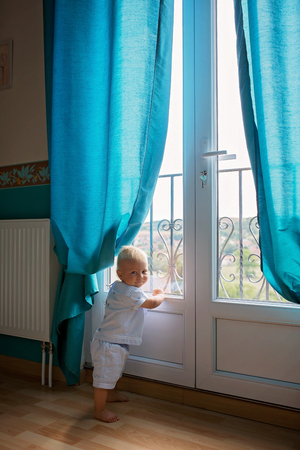 Baby child reading a book at home. Boy studying on blue background Stockfoto