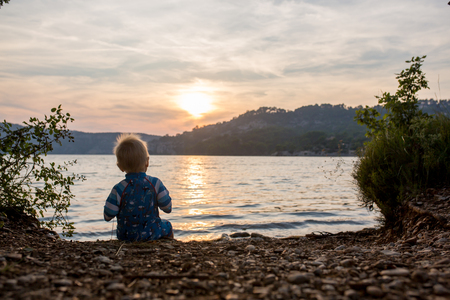 Cute child, toddler boy, enjoying the sunset over a lake, summertime