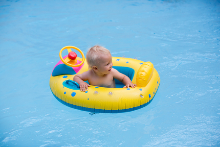 Cute child, playing with inflatable boat in pool, holiday vacation 版權商用圖片