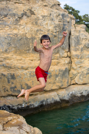 Boy jumping to the lake. Child jumping off a cliff into the sea. Summer fun lifestyle