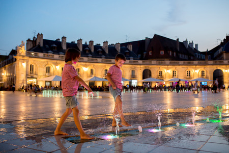 Children, refreshing on a very hot summer day, walking in fountain, playing with water at night, summertime Stok Fotoğraf