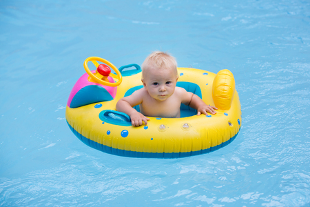 Cute child, playing with inflatable boat in pool, holiday vacation Stock Photo