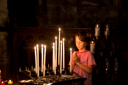 Little boy prays and puts a candle in Orthodox Church, sad kid with faith 版權商用圖片