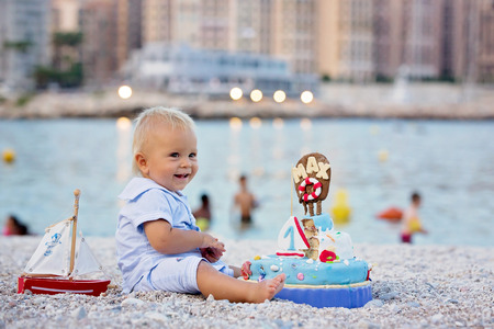 Sweet baby boy, celebrating on the beach first birthday with sea theme cake and sea decoration Stock Photo