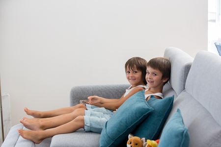 Sweet children, sitting on couch in sunny living room, playing on tablet at home Stock Photo