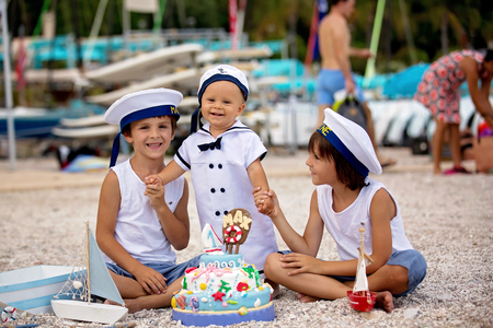Sweet baby boy and his brothers, celebrating on the beach first birthday with sea theme cake and sea decoration