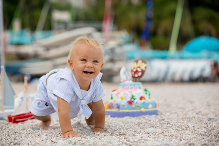Sweet baby boy, celebrating on the beach first birthday with sea theme cake and sea decoration Banco de Imagens