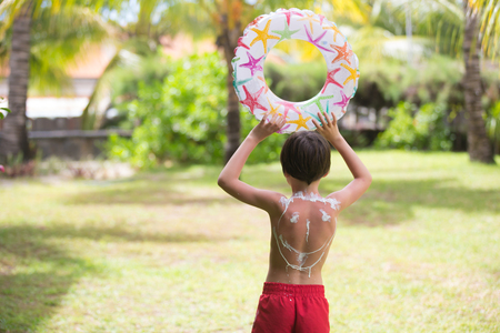 Child with suntan lotion shaped as smile on his back, going at the beach with toys and inflatable ring. Concept for sun protection and skin care for children