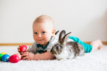 Kleines Kleinkindkind, Baby, zu Hause spielend mit Häschen und Ostereiern, bunte Handzeichnungen auf den Eiern Standard-Bild