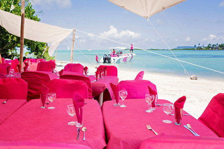 Tables, set for lunch at the beach near quiet lagoon Stock Photo