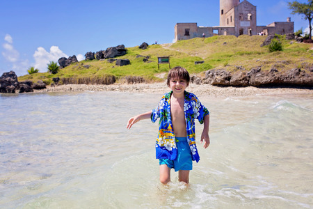 Clear turquoise water iSweet fashion child in clear turquoise water in Mauritius island with tree and light house on a small islandn Mauritius island with tree and light house on a small island