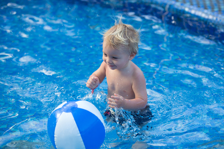 Adorable happy little child, toddler boy, having fun relaxing and playing in a pool on sunny day during summer vacation in resort Stock Photo