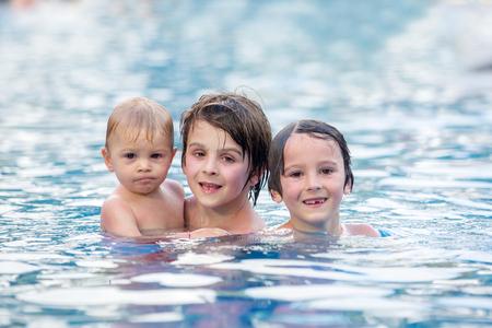 Entzückendes glückliches kleines Kind, Kleinkindjunge, der Spaß hat, sich zu entspannen und mit seinen älteren Brüdern in einem Pool an einem sonnigen Tag während der Sommerferien im Resort zu spielen? Standard-Bild