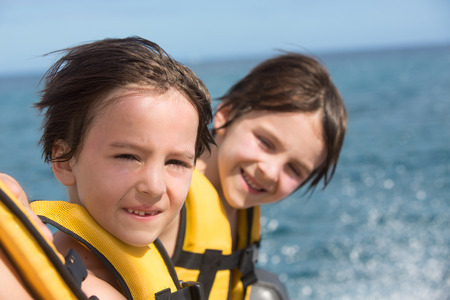 Happy family with life vests, having fun on a boat trip while on holiday in Mauritius Stock Photo