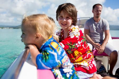 Felice bella famiglia di moda, bambini e genitori, vestiti con camicie hawaiane, godendosi una gita di un giorno con il motoscafo a Mauritius