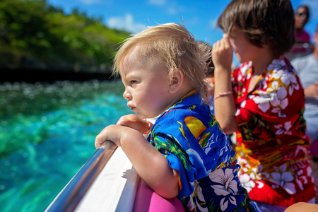 Happy beautiful fashion family, children and parents, dressed in hawaiian shirts, enjoying day trip with speed boat in Mauritius Imagens
