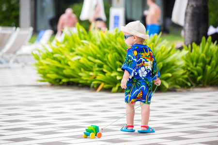 Adorable toddler boy in summer holiday resort in Mauritius, casually dressed, had and sunglasses 写真素材