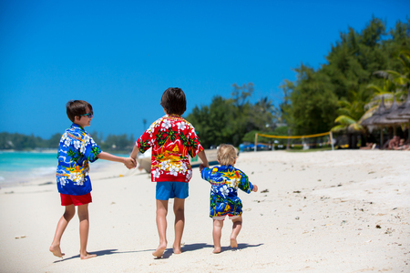 Happy beautiful fashion children, dressed in hawaiian shirts, playing together on the beach, famiy joyful vacation