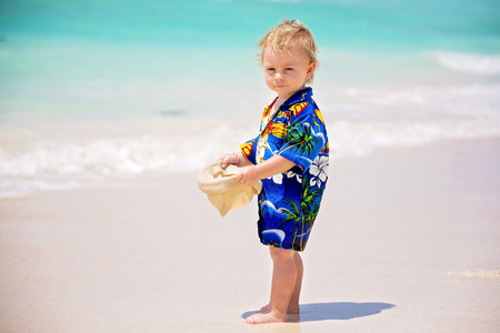 Adorable toddler boy in summer holiday resort in Mauritius, casually dressed, had and sunglasses Stock Photo