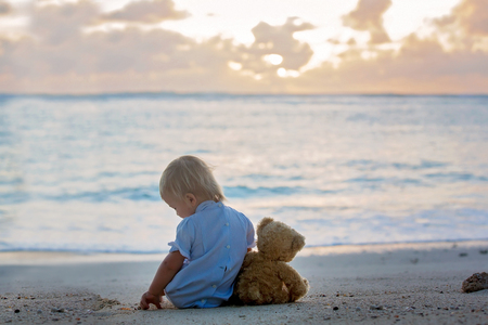 Happy beautiful fashion kid, child, casually dressed, enjoying the sunrise on the beach in Mauritius, family joyful vacation