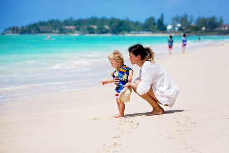 Mother and child playing at tropical beach. Family sea summer vacation. Mom and kid, toddler boy, play in the water. Ocean and water fun for parent and kids. Fit and healthy family at exotic beach