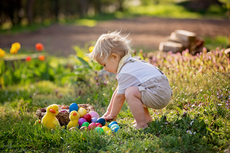 Sweet toddler boy with bunny ears, egg hunting for Easter, child and Easter day traditions. Kids and holidays Stock Photo
