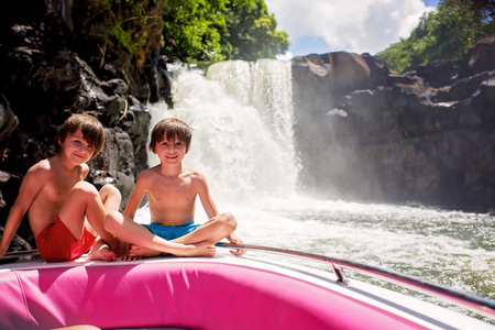 Children, enjoying the waterfall, near the island of Mauritius from a boat trip. Family vacation. Quality family time Stockfoto