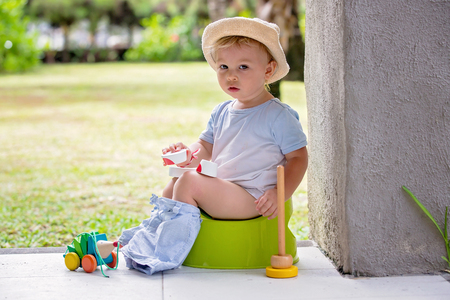 Sweet toddler boy, sitting on potty on a back porch in a holiday resort patio, playing with toys