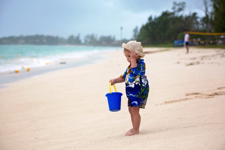 Cute toddler baby boy playing with beach toys on tropical beach in Mauritius