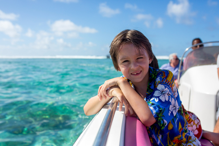 Happy beautiful fashion family, children and parents, dressed in hawaiian shirts, enjoying day trip with speed boat in Mauritius Stock Photo